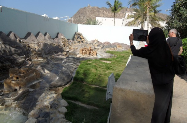 A young woman in her black abayah taking a photo with her Ipad is one way ot describing Oman today