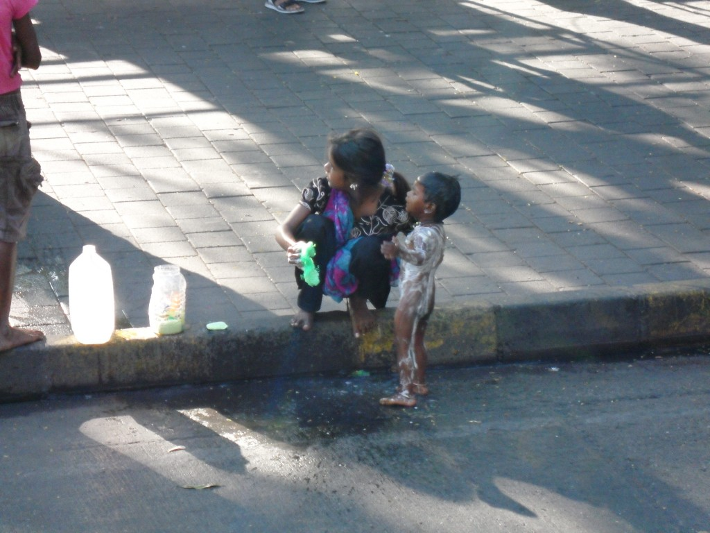 A young girl soaping down her baby brother (or child) on the street is not an unusual sight in Mumbai